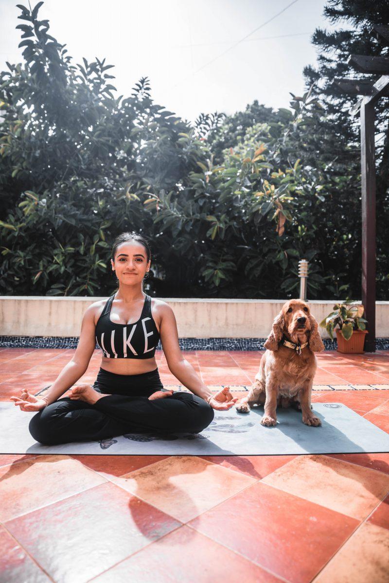 young woman meditating with dog scopio 2ad1ed1e f2a0 464d bb2e 8faf02922315 scaled - Ter um cachorro ajuda a manter seu coração mais saudável